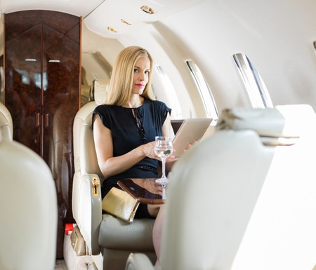 happy rich woman: Portrait of rich mid adult woman using tablet computer in private jet