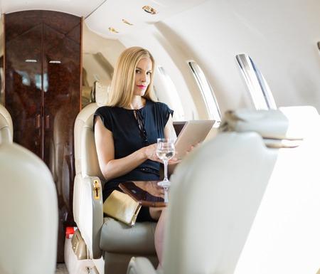 donna ricca: Ritratto di donna ricca metà degli adulti utilizzando il computer tablet in jet privato Archivio Fotografico