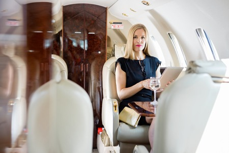 Portrait of wealthy mid adult woman holding tablet computer in private jet Stock Photo