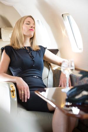 rijke vrouw: Mooie rijke vrouw met gesloten ogen ontspannen in prive-jet