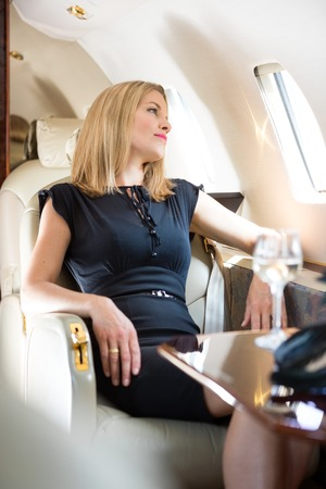 Beautiful rich woman looking through window in private jet Stock Photo