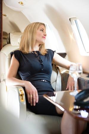 rijke vrouw: Mooie rijke vrouw kijkt door raam in de prive-jet