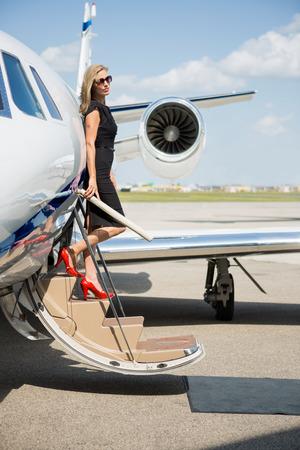 rijke vrouw: Volledige lengte van rijke vrouw uitstappen prive-jet op de luchthaven terminal