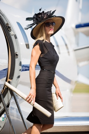 Side view portrait of wealthy woman getting off private jet at airport terminal photo