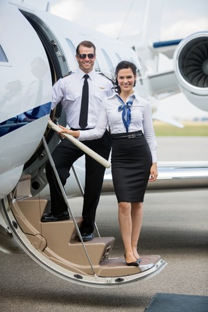 airline pilot: Full length portrait of confident airhostess and pilot standing on ladder of private jet at airport terminal