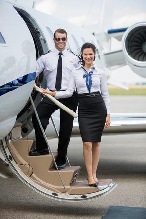 Ritratto integrale di airhostess fiducioso e pilota in piedi sulla scaletta del jet privato al terminal dell'aeroporto