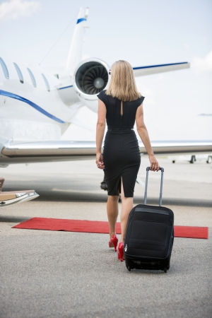 Rear view of wealthy woman with luggage walking towards private jet at airport terminal photo