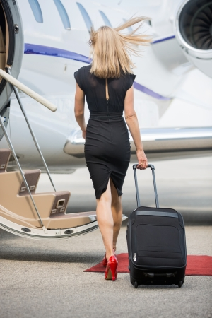 Full length rear view of rich woman with luggage walking towards private jet at airport terminal photo