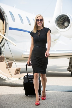 Full length portrait of rich woman with luggage walking against private jet at airport terminal