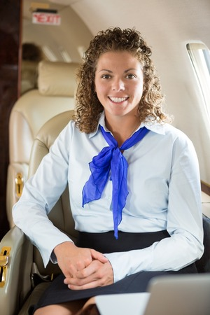 an attendant: Portrait of happy airhostess sitting in private jet