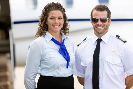 flight attendant: Portrait of confident stewardess and pilot standing against private jet