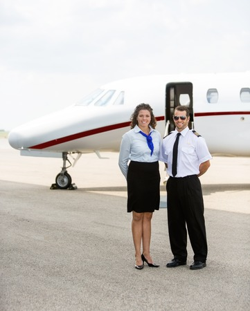 Full length portrait of confident airhostess and pilot standing together against private jet photo