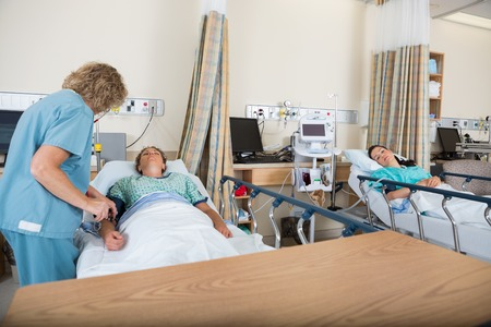 health care facility: Mature nurse examining patient in post anesthesia care unit Stock Photo