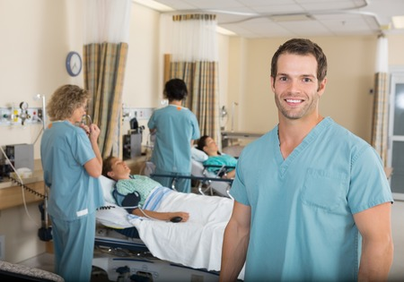 Portrait of young male nurse with colleagues examining patients in PACU Stock Photo - 25768935