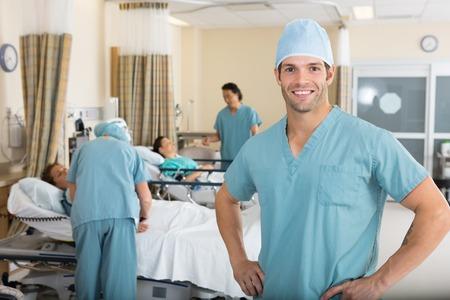 enfermera con cofia: Retrato de la enfermera de sexo masculino confidente con sus colegas examinaron los pacientes en la sala
