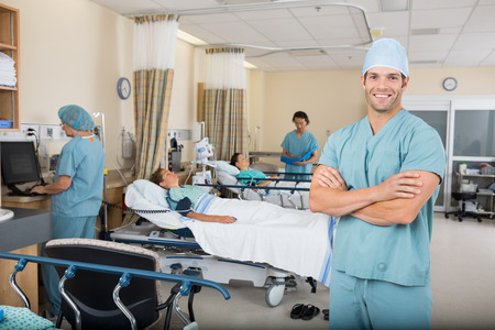 Portrait of confident male nurse with colleagues and patients in hospital ward Stock Photo - 25768939