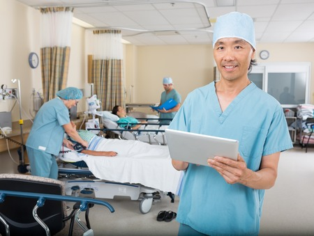 pacu: Portrait of male nurse with digital tablet standing in hospital PACU