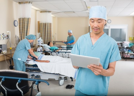 pacu: Mid adult male nurse using digital tablet in hospital ward