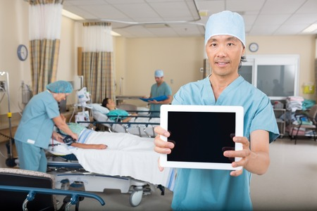 pacu: Portrait of mid adult male nurse showing digital tablet in hospital ward