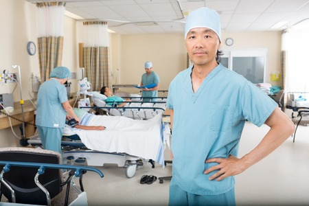 Portrait of confident male nurse colleagues examining patients in hospital ward Stock Photo - 25769015