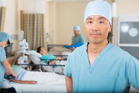 Portrait of confident mid adult male nurse with colleagues examining patients in hospital ward