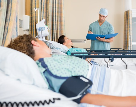pacu: Female patients lying on bed while nurse examines report in hospital ward. Stock Photo
