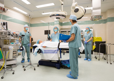 staging: Surgical team preparing for sugery in operating theater
