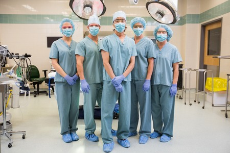 Full length portrait of confident medical team standing in operation room photo