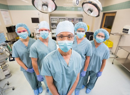 Portrait of confident medical team in scrubs standing inside operation room photo