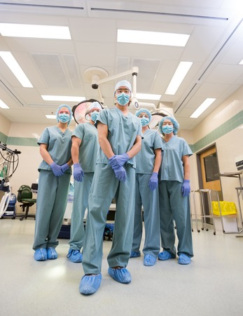 Low angle portrait of medical team in scrubs standing inside operation room photo