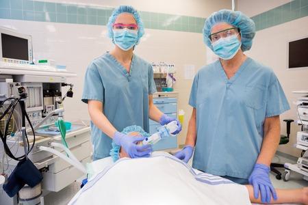 anesthetist: Portrait of nurses adjusting oxygen mask on female patient in operation room