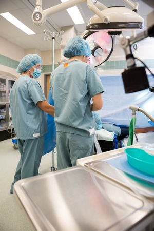 Rear view of female nurses preparing patient before operation in hospital photo
