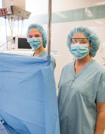 enfermera con cofia: Anestesiólogo de pie detrás de la cortina en la sala de operaciones