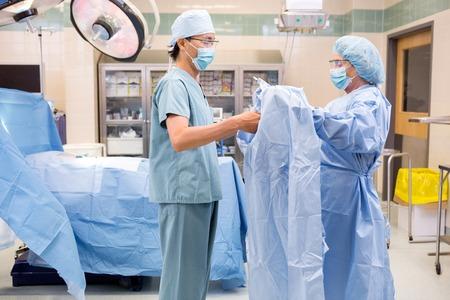 surgical: Instrumentista asistir cirujano con bata estéril en quirófano