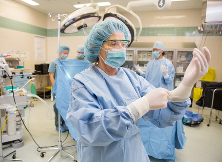 operation gown: Mature female surgeon adjusting latext gloves in surgical theater Stock Photo