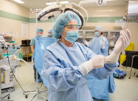 Maturo chirurgo femmina regolazione guanti in latex in sala operatoria