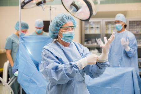 Mature female doctor wearing surgical gloves with team standing in background at operation room photo