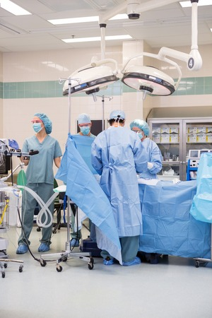 Surgical team operating on patient in theater photo