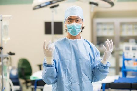 operation gown: Retrato de mediados de cirujano adulto en bata quir�rgica de pie en la sala de operaciones