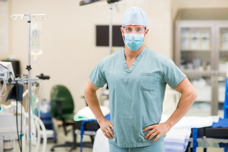 anesthetist: Portrait of confident male surgeon with hands on hips standing in operation room