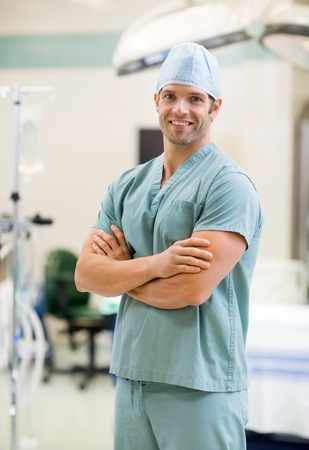 hospital gown: Portrait of smiling surgeon standing arms crossed in operation room