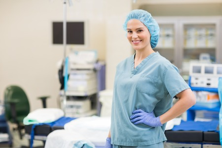 enfermera con cofia: Retrato del cirujano hermosa con la mano en la cadera de pie en la sala de operaciones