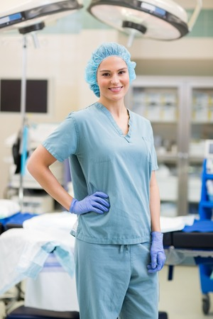 enfermera con cofia: Retrato del cirujano confidente con la mano en la cadera en la sala de operación Foto de archivo