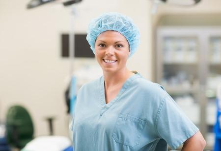 surgical: Retrato de la hermosa joven miembro del equipo quirúrgico de pie en la sala de operaciones