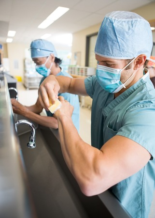Antibacterial: Medical staff sterilizing hands and arms before surgery Stock Photo