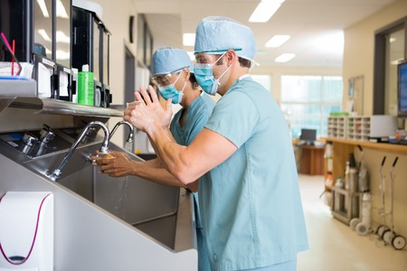 Side view of surgeons scrubbing hands before surgery in hospital Stock Photo