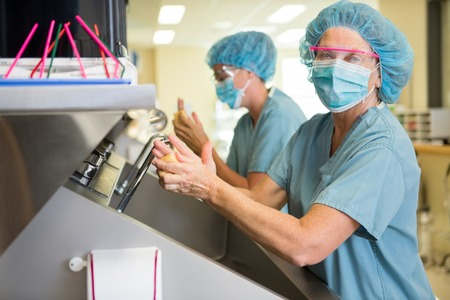 surgical nurse: Portrait of female doctor washing hands with colleague before surgery in hospital