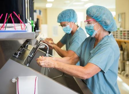 I membri del team chirurgico di lavaggio braccia e le mani prima di un'operazione chirurgica Archivio Fotografico