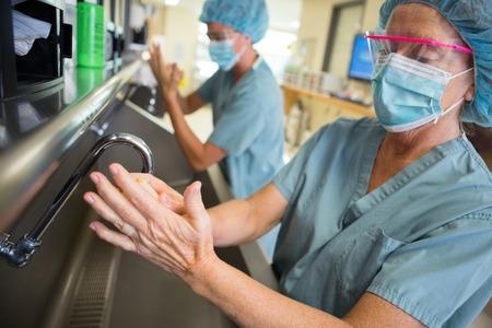 Doctor maduro restregar las manos con su colega en el lavabo antes de la cirugía en el hospital