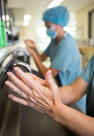 washing hands: Detail of surgeon doing a surgical scrub on hands and arms Stock Photo